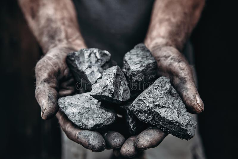 Miner holds coal palm. Concept mining. Top view. stock image