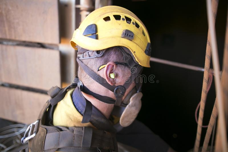Miner worker wearing a ear plug noise safety protection when working near operating life plant machinery royalty free stock photography