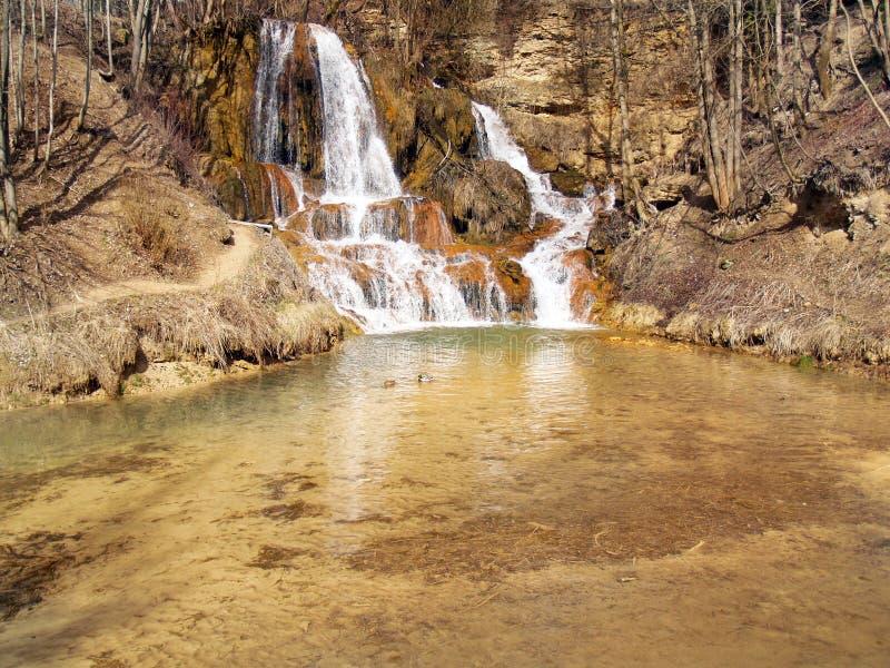 Mineraal-rijke waterval in Gelukkig dorp stock fotografie