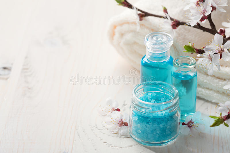 Mineral bath salts, shower gel, towels and flowers on the wooden table royalty free stock images