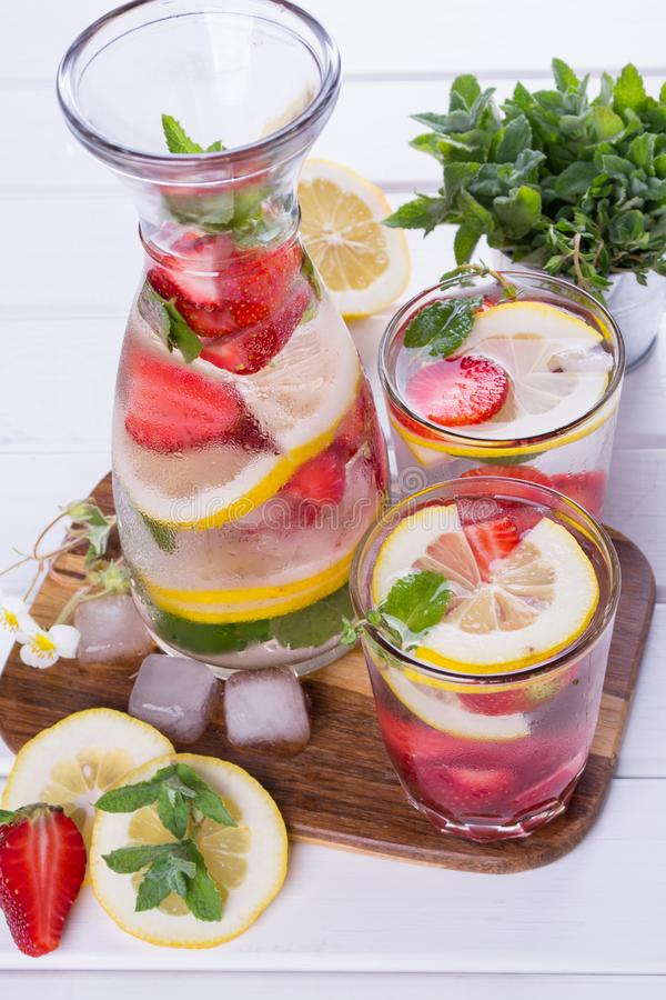 Mineral infused water with strawberry, ice, herb and mint leaves on white background, homemade detox soda stock photography