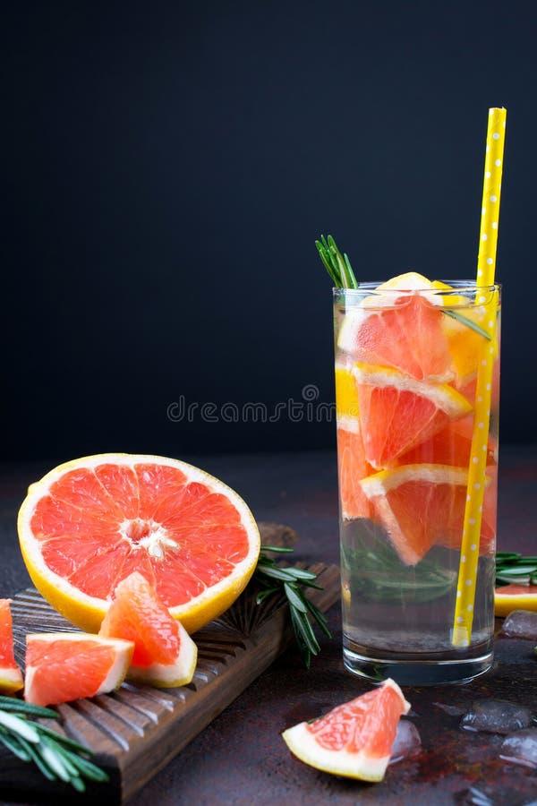 Mineral ingav vatten med grapefruktis och rosmarin på mörk bakgrund, hemlagat detoxsodavattenvatten royaltyfri foto