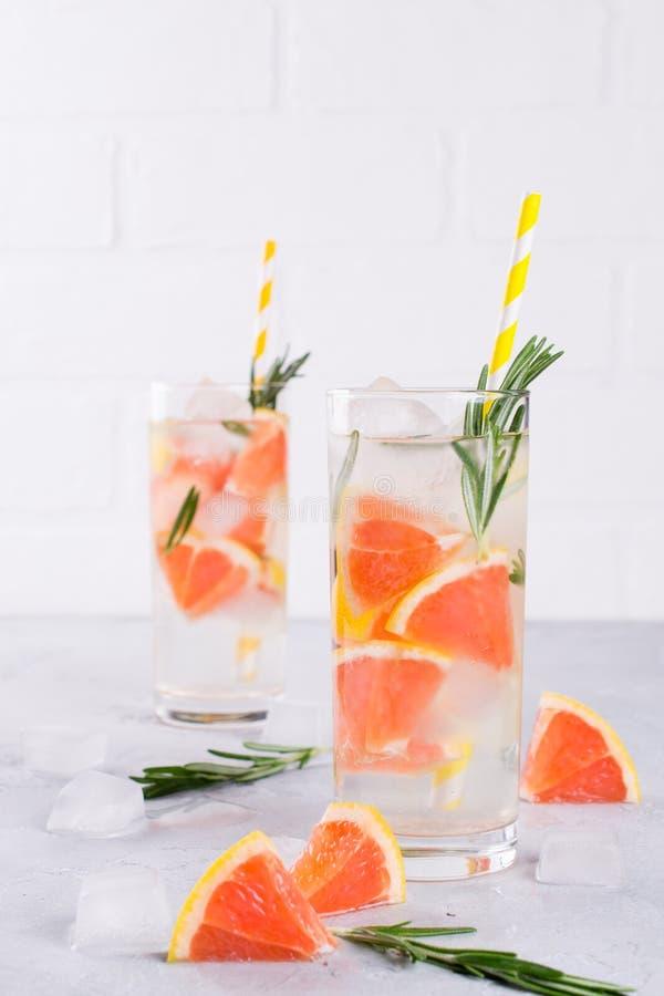 Mineral ingav vatten med grapefruktis och rosmarin på vit bakgrund, hemlagat detoxsodavattenvatten royaltyfri bild