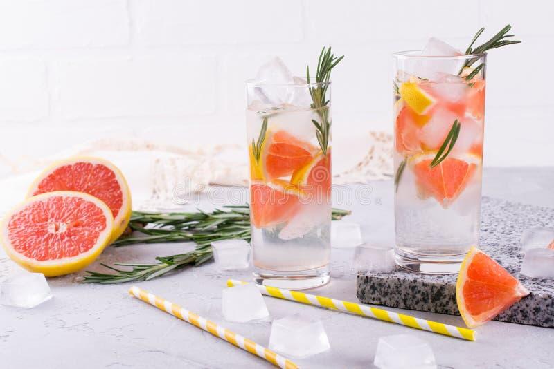 Mineral ingav vatten med grapefruktis och rosmarin på vit bakgrund, hemlagat detoxsodavattenvatten royaltyfria bilder