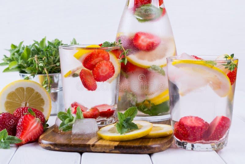 Mineral ingav vatten med jordgubbe-, is-, ört- och mintkaramellsidor på vit bakgrund, hemlagad detoxsodavatten arkivbild