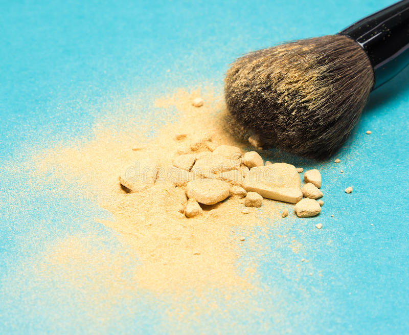 Mineral shimmer powder golden color with makeup brush. Close-up of crushed mineral shimmer powder golden color with makeup brush on blue background royalty free stock photography