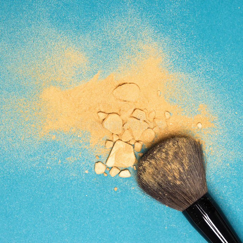 Mineral shimmer powder golden color with makeup brush. Close-up of crushed mineral shimmer powder golden color with makeup brush on blue background royalty free stock photos