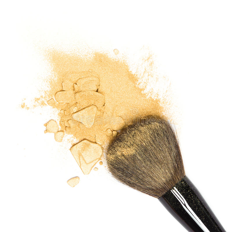 Mineral shimmer powder golden color with makeup brush. Close-up of crushed mineral shimmer powder golden color with makeup brush on white background royalty free stock photos
