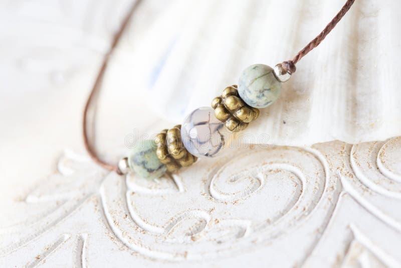 Mineral stone beads yoga bracelet detail. On decorative background stock photos