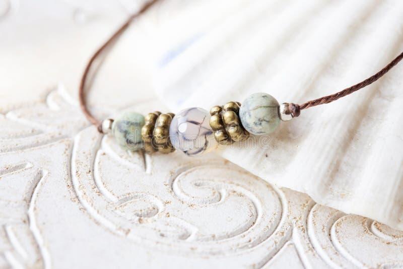 Mineral stone beads yoga bracelet detail. On decorative background royalty free stock photo