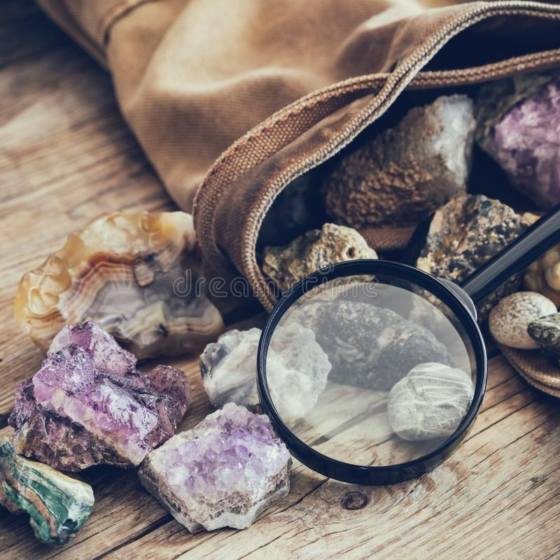 Mineral stones set and magnifying glass, backpack of geologist. Mineral stones: turquoise, morion, smoky quartz, rhinestone, chalcedony, fluorite, agate stock photo