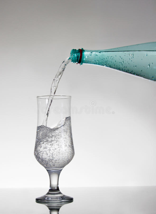 Mineral water. Pouring mineral water into glass stock images