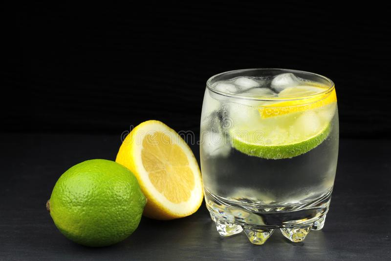 Mineral water in the glass with ice cubes, lime and lemon stock images