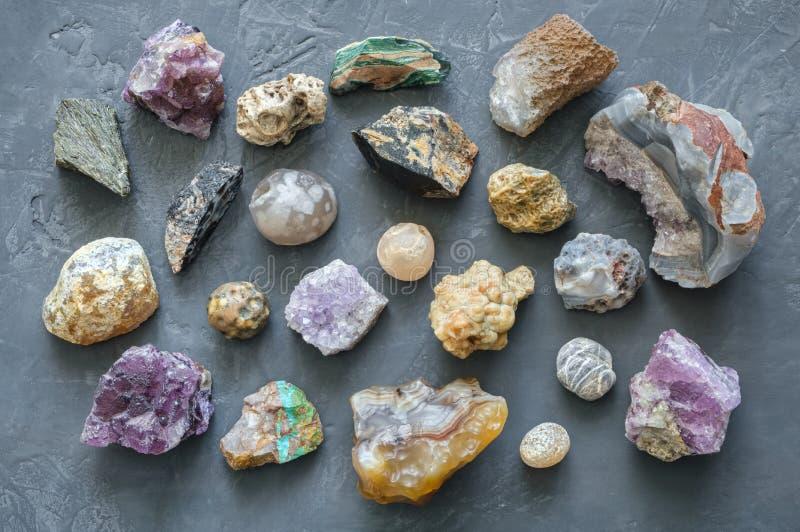 Minerale steneninzameling: turkoois, morion, agaat, onyx en chalcedony op grijze concrete achtergrond stock afbeelding