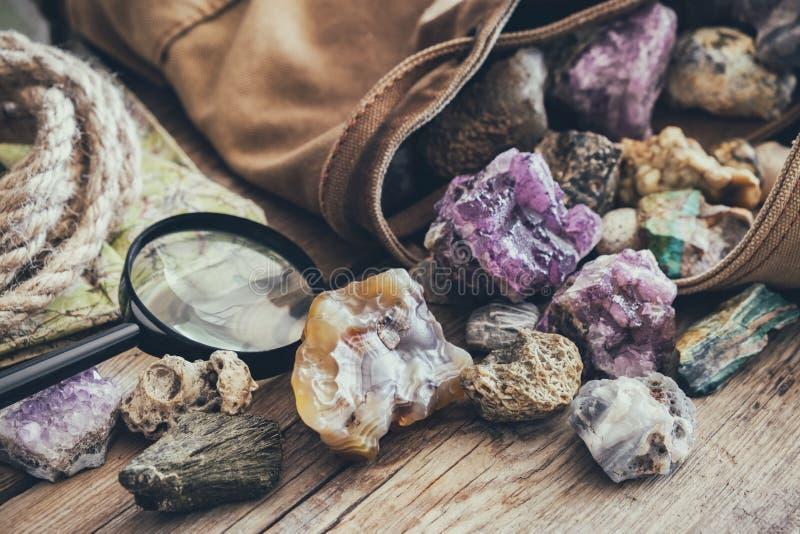 Mineraliska stenar samling och sats av geologen - ryggsäck, översikt, förstoringsglas, rep arkivfoto