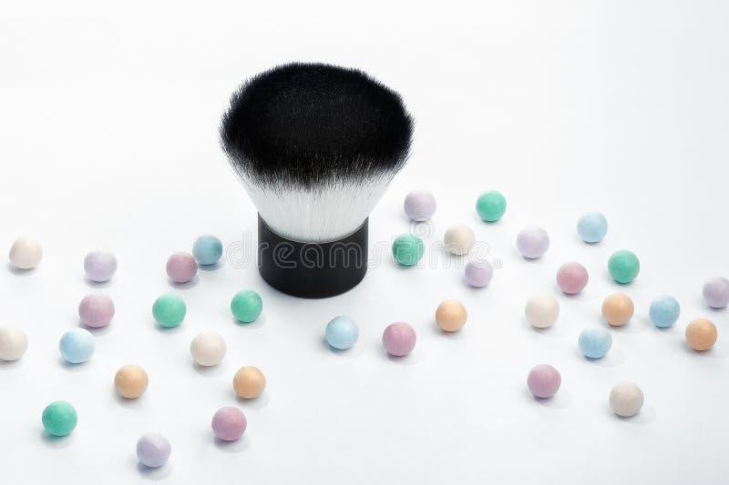 Mineralpulverperlen und kabuki Make-upbürste, herauf nahe Ansicht lizenzfreie stockfotografie