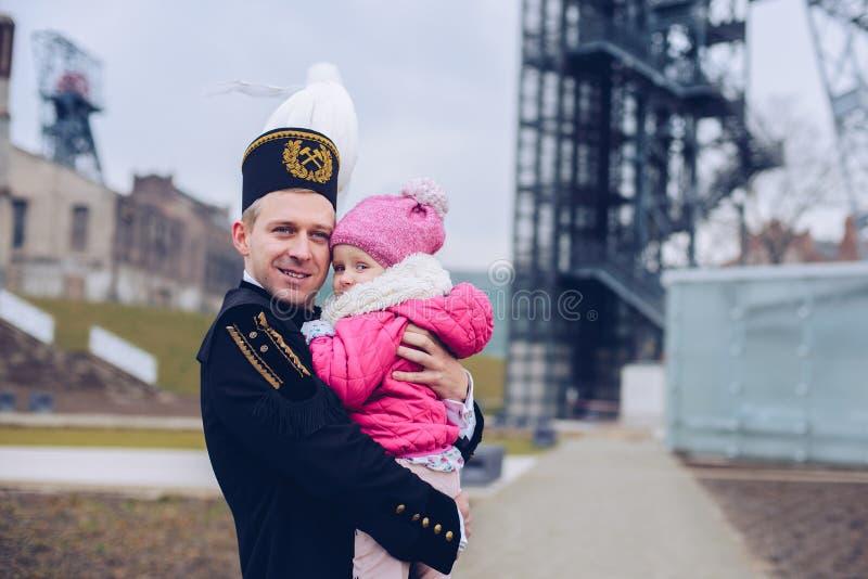Minero negro del capataz del carbón en uniforme de la gala con su niño fotos de archivo