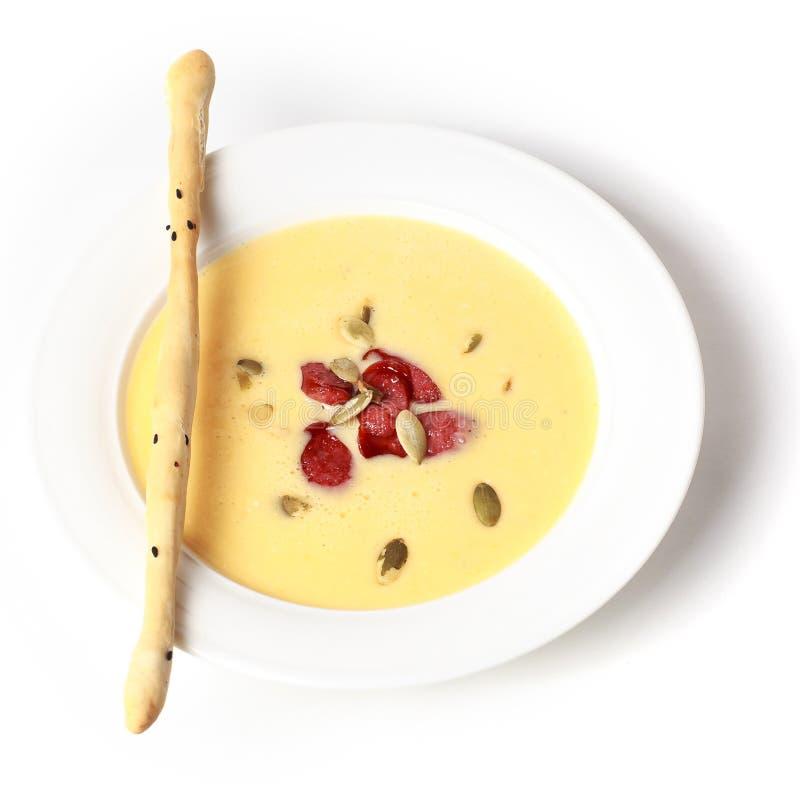 Minestra arrostita della carota e della zucca con i semi delle salsiccie, del grissino e di zucca Isolato su priorità bassa bianc immagine stock libera da diritti