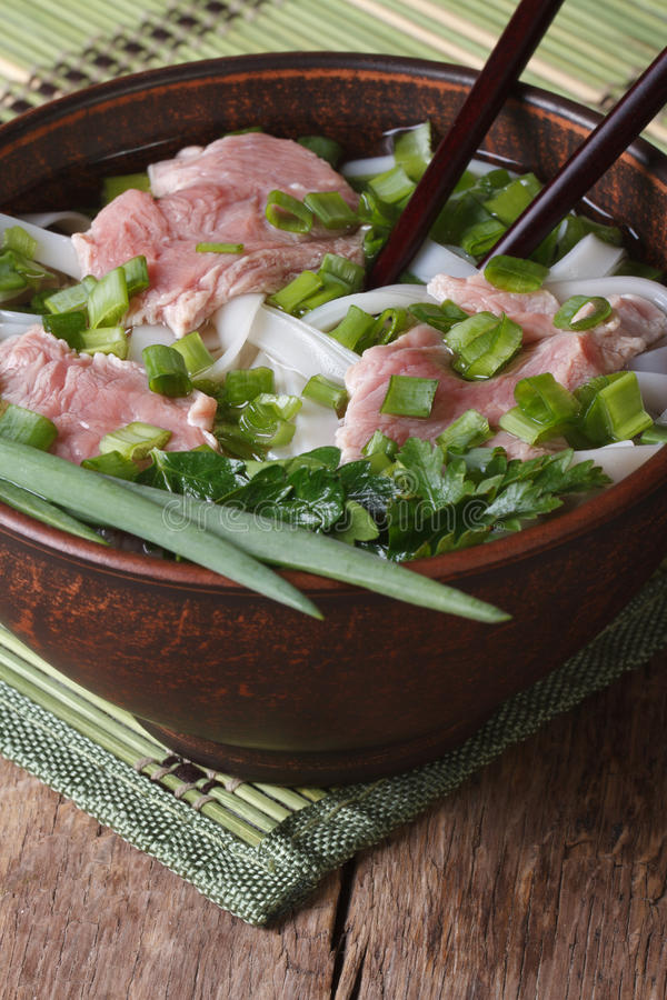 Minestra asiatica con carne, le tagliatelle di riso e le erbe fresche verticale fotografie stock libere da diritti