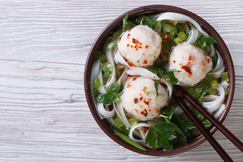 Minestra asiatica con la vista superiore delle palle di pesce e delle tagliatelle di riso fotografia stock libera da diritti