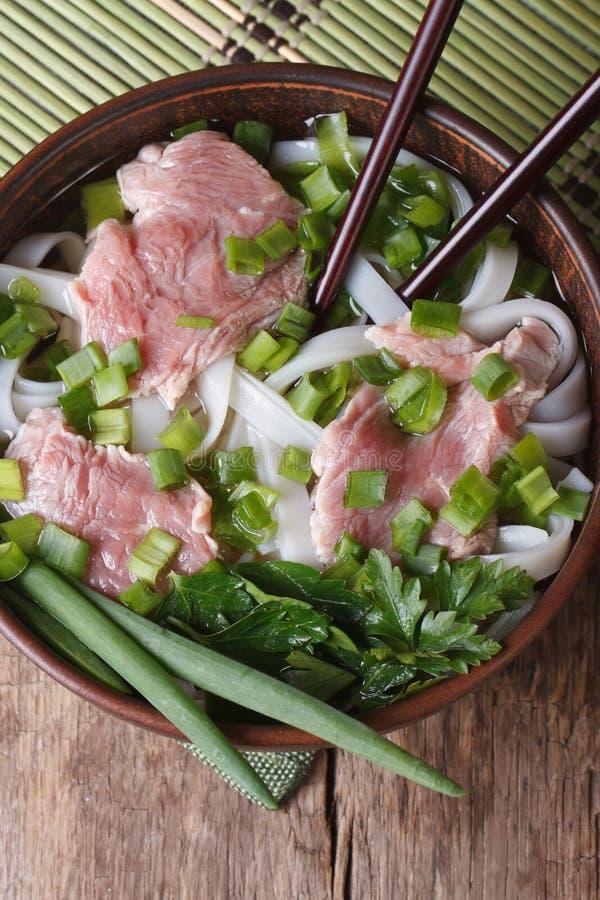 Minestra asiatica con manzo, le tagliatelle di riso e la vista superiore delle erbe fotografia stock libera da diritti