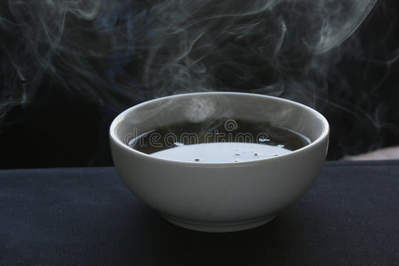 Minestra calda in una ciotola ceramica bianca su fondo nero fotografia stock