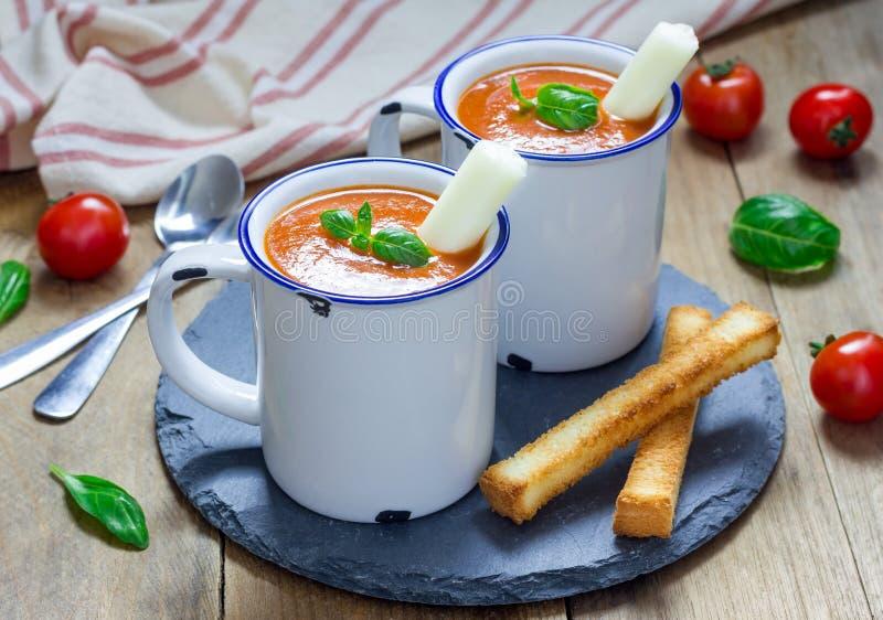 Minestra casalinga del basilico del pomodoro nella tazza, servita con il bastone del formaggio della mozzarella fotografia stock libera da diritti