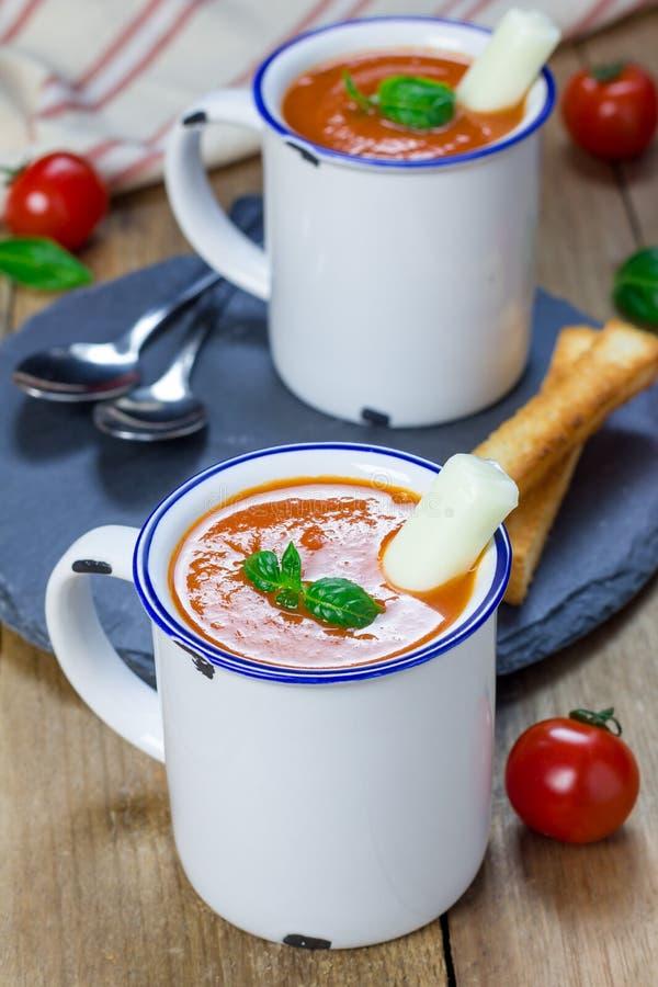 Minestra casalinga del basilico del pomodoro nella tazza, servita con il bastone del formaggio della mozzarella fotografie stock libere da diritti