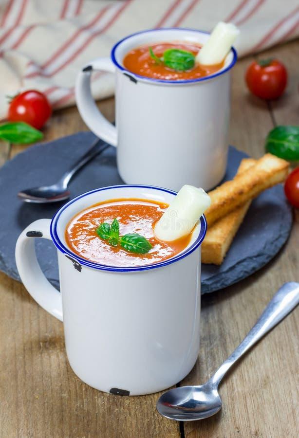 Minestra casalinga del basilico del pomodoro nella tazza, servita con il bastone del formaggio della mozzarella fotografia stock