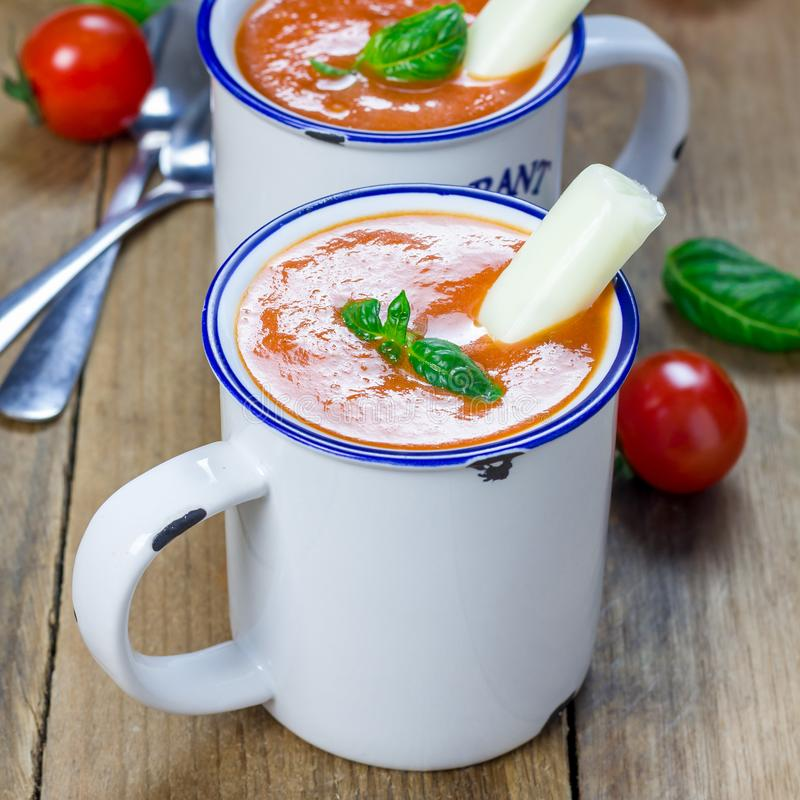 Minestra casalinga del basilico del pomodoro nella tazza, servita con il bastone ed i crostini del formaggio della mozzarella, fo fotografie stock