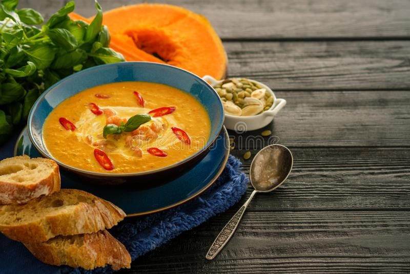 Minestra casalinga deliziosa della zucca con la prateria dei gamberetti, del peperoncino rosso e del basilico immagine stock libera da diritti