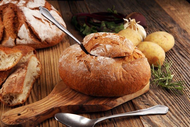 Minestra casalinga della crema della patata, servita in ciotola del pane fotografie stock
