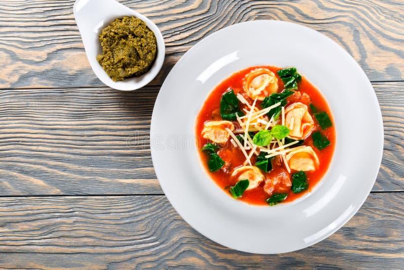 Minestra con le salsiccie italiane, spinaci, pomodoro, parmigiano, pesto-salsa dei tortellini fotografia stock