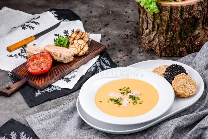 Minestra crema con il salmone in un piatto bianco su fondo concreto scuro immagini stock libere da diritti