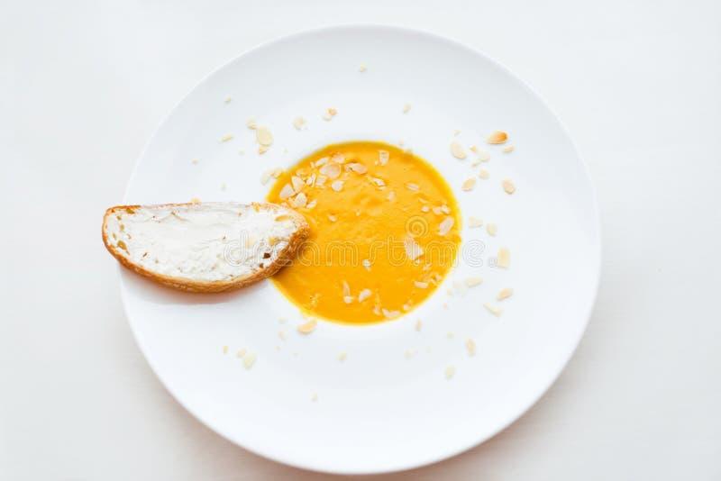Minestra crema della cipolla con la minestra crema di verdure del pane tostato con la zucca in una ciotola bianca e una fetta di  fotografie stock libere da diritti