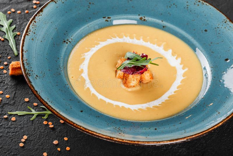 Minestra crema delle lenticchie con il pangrattato sul piatto su fondo di pietra grigio scuro immagine stock