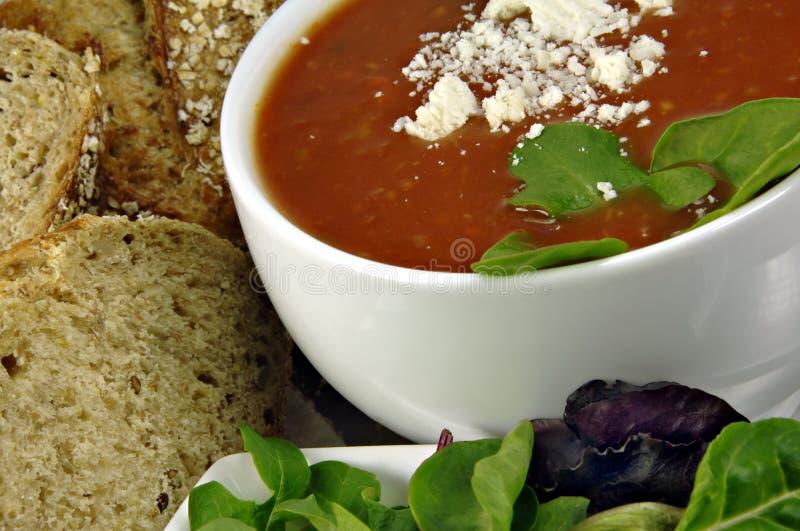 Minestra del basilico del pomodoro con pane ed insalata immagine stock