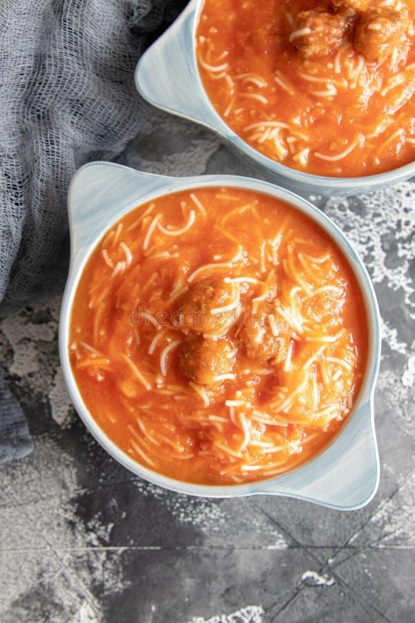 Minestra del pomodoro con le tagliatelle e le polpette immagini stock