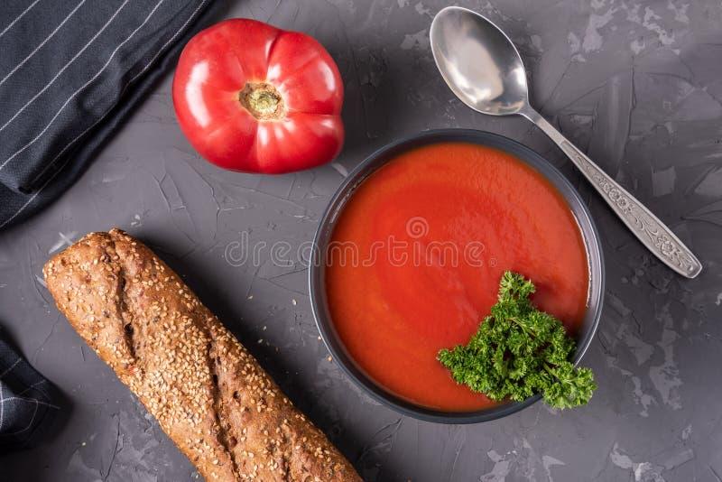 Minestra del pomodoro con prezzemolo in una vista superiore della ciotola ceramica nera fotografia stock