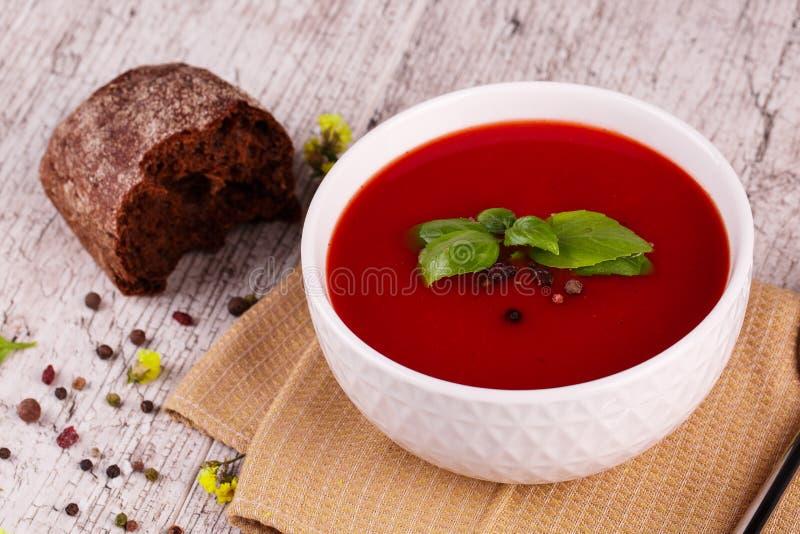 Minestra di Gazpacho Zuppa di verdure fredda piccante rossa fresca con basilico e pane su un fondo della tavola immagini stock libere da diritti