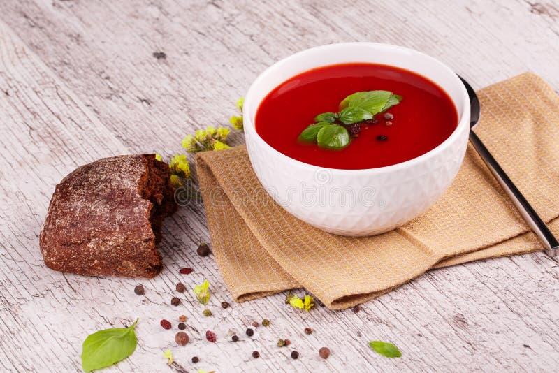 Minestra di Gazpacho Zuppa di verdure fredda piccante rossa fresca con basilico e pane su un fondo della tavola fotografia stock libera da diritti