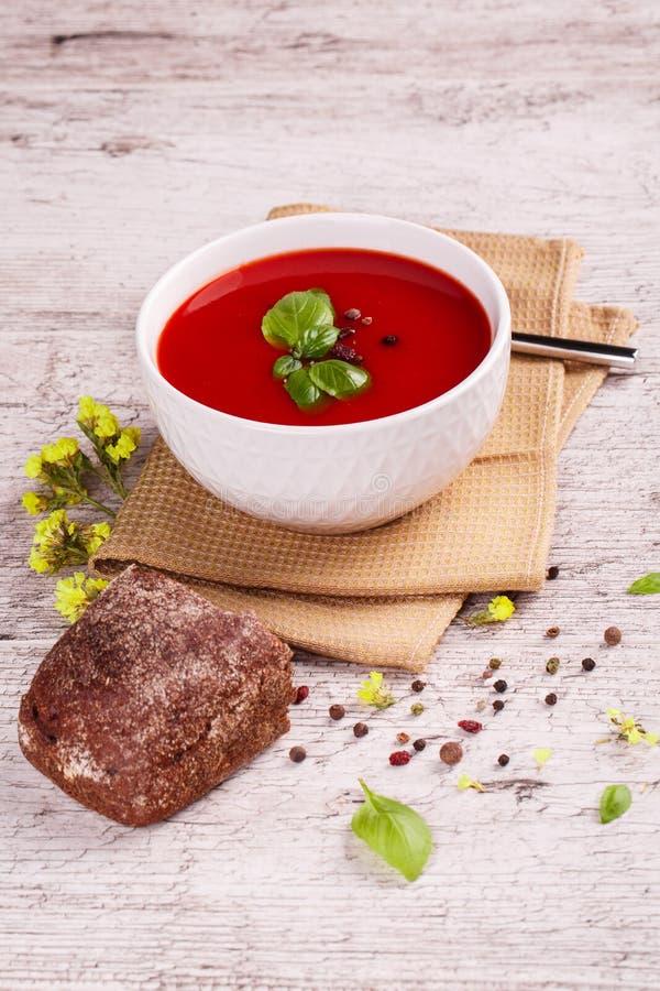 Minestra di Gazpacho Zuppa di verdure fredda piccante rossa fresca con basilico e pane su un fondo della tavola immagine stock libera da diritti