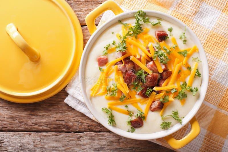 Minestra di patate crema con il primo piano del cheddar e del bacon horizo fotografia stock