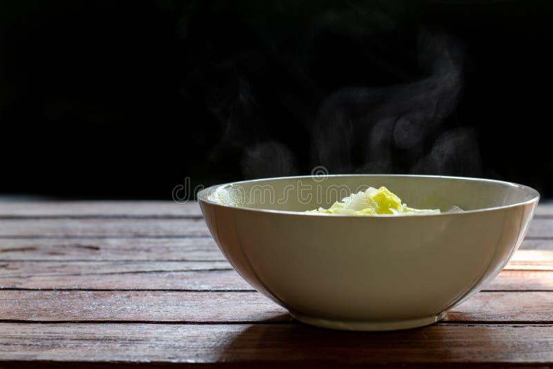 Minestra di verdura calda in ciotola ceramica bianca sulla tavola e sul fumo di legno Fuoco selettivo, spazio della copia fotografia stock