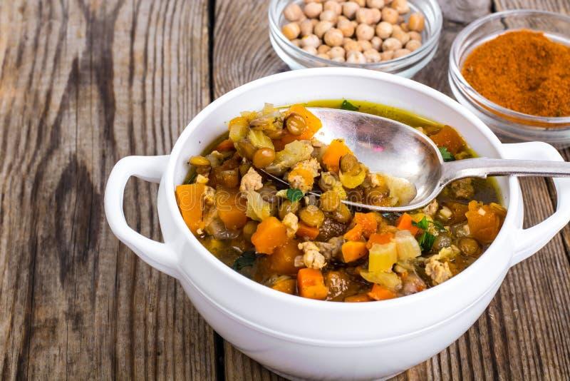 Minestra piccante con i ceci, la zucca ed il curry in una ciotola bianca sopra immagine stock libera da diritti