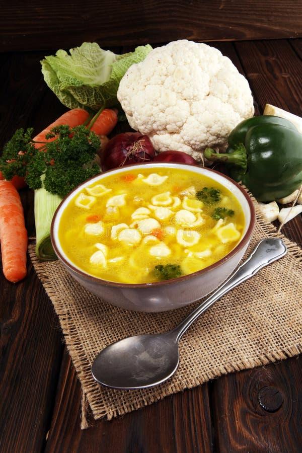 Minestra pura con il pollo e le tagliatelle Brodo con le carote, vari ortaggi freschi delle cipolle in un vaso fotografia stock libera da diritti