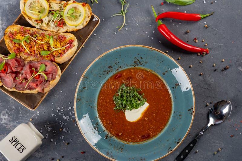Minestra tradizionale del pomodoro con i peperoncini rossi e la Bruschetta fotografia stock libera da diritti