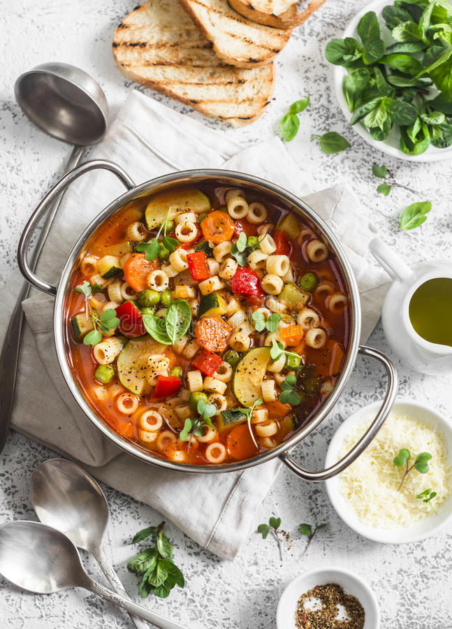 Minestrone soup in a pan on a light table, top view. Delicious vegetarian food concept. royalty free stock photos