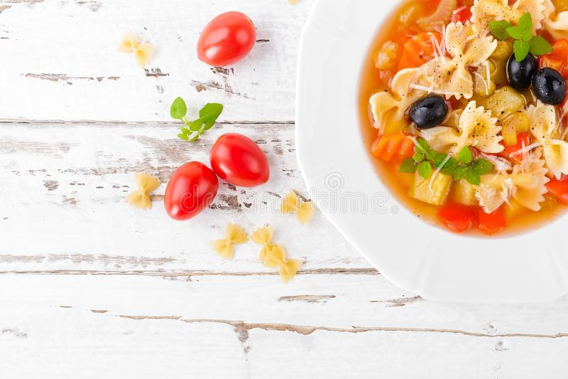 Minestrone, vegetarian soup with pasta and vegetables on white wooden rustic background. Traditional italian food royalty free stock photos
