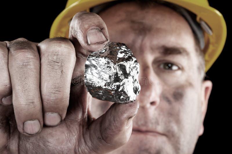 Mineur argenté avec la pépite photographie stock